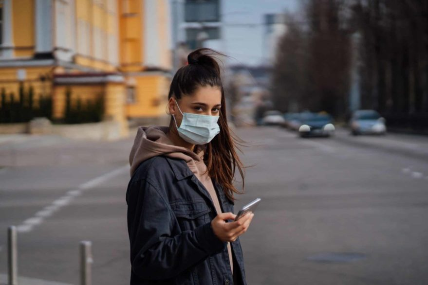 Girl in protective mask using smartphone outdoors.