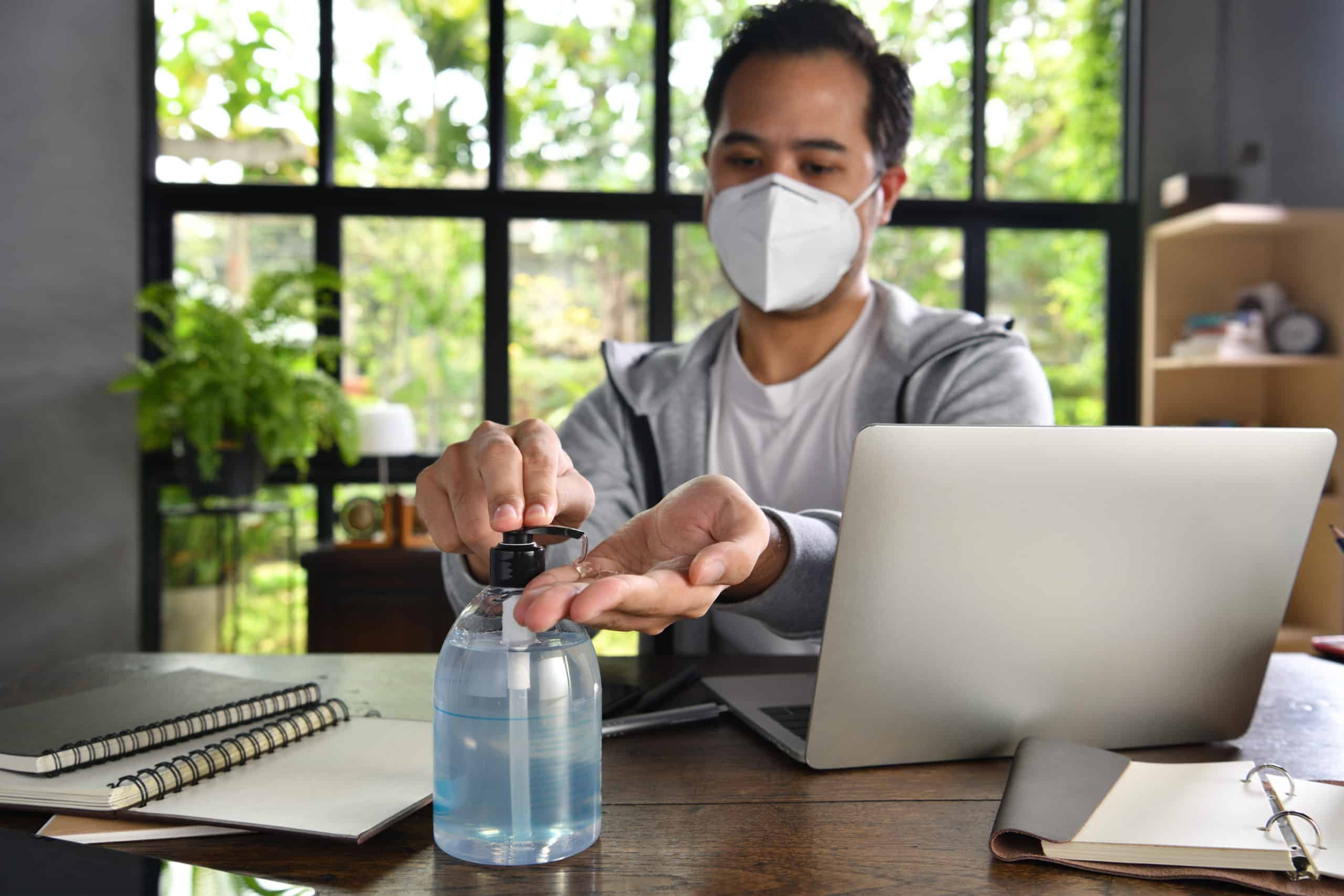 Asian man in quarantine and social distancing wearing surgical mask and cleaning hands with alcohol gel sanitizer while working from home during Covid-19 Coronavirus pandemic